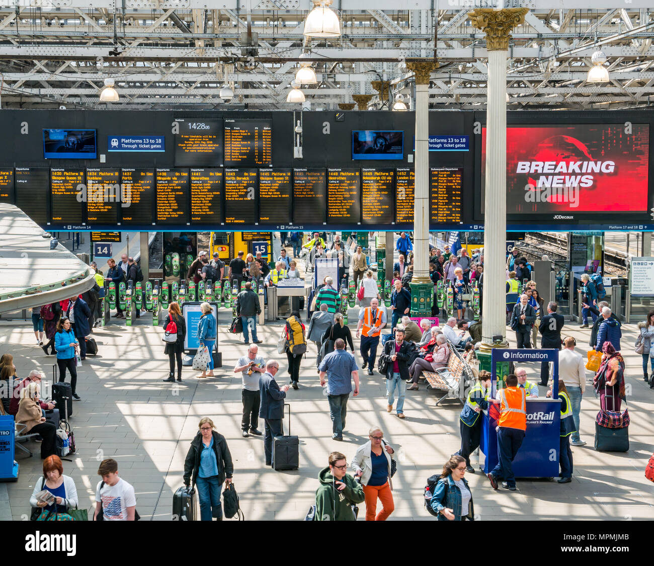Passengers in busy main concourse, Waverley Railway Station, Edinburgh, Scotland, UK with breaking news headline on giant TV screen - Stock Image