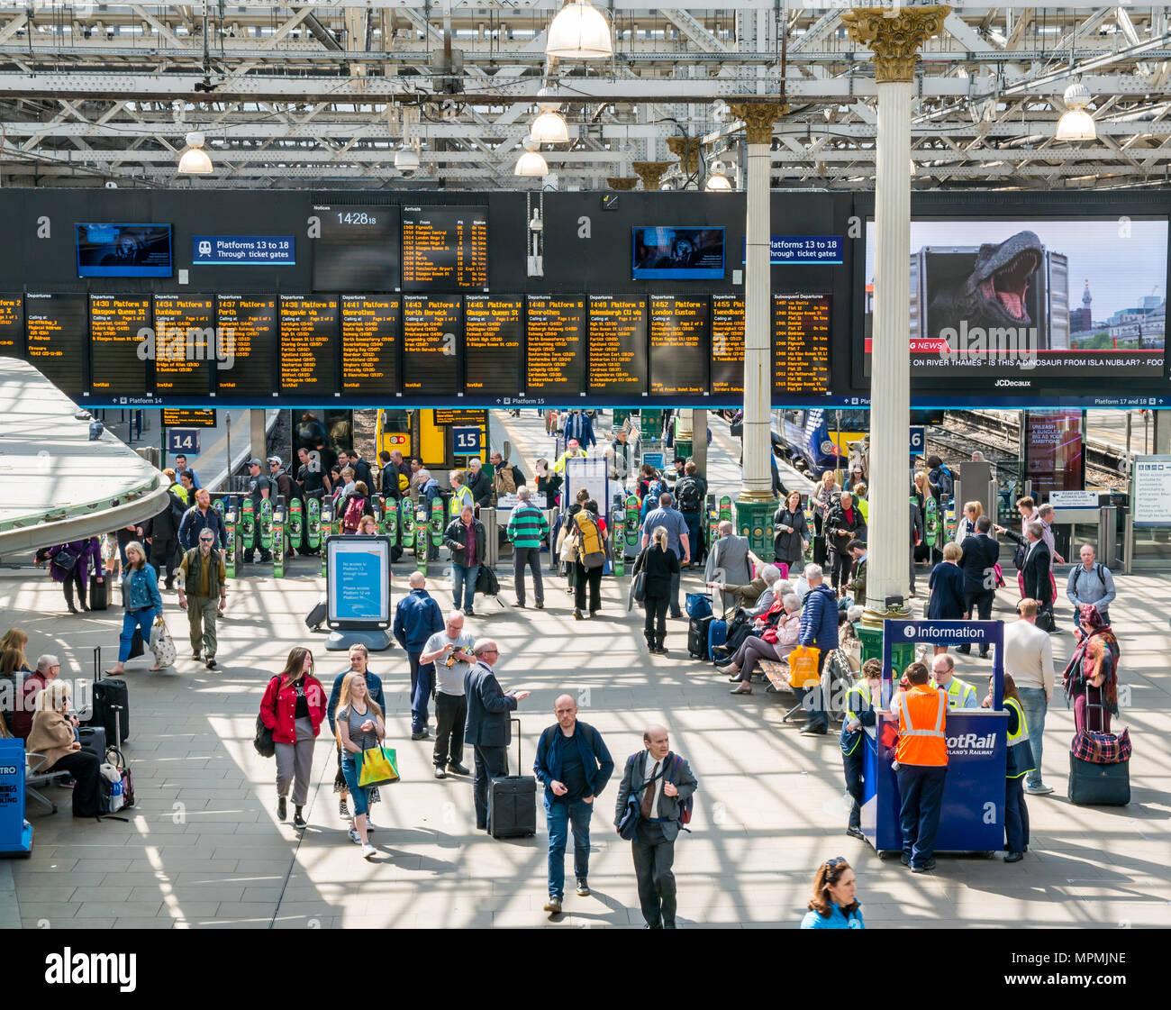 Passengers in busy main concourse, Waverley Railway Station, Edinburgh, Scotland, UK with Jurassic Park Isla Nublar on giant TV screen - Stock Image