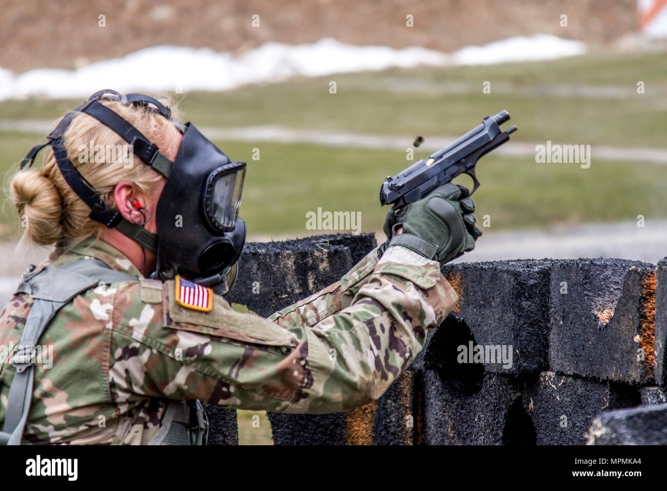 Spec. Courtney Natal fires the M-9 pistol while wearing a protective mask during the stress shoot lane, combining physical tests and shooting events during the New York Army National Guard  Best Warrior Competition at Camp Smith Training Site March 30, 2017. The Best Warrior competitors represent each of New York's brigades after winning competitions at the company, battalion, and brigade levels. At the state level they are tested on their physical fitness, military knowledge, endurance, marksmanship, and land navigation skills. The two winners of the competition, one junior enlisted and one N Stock Photo