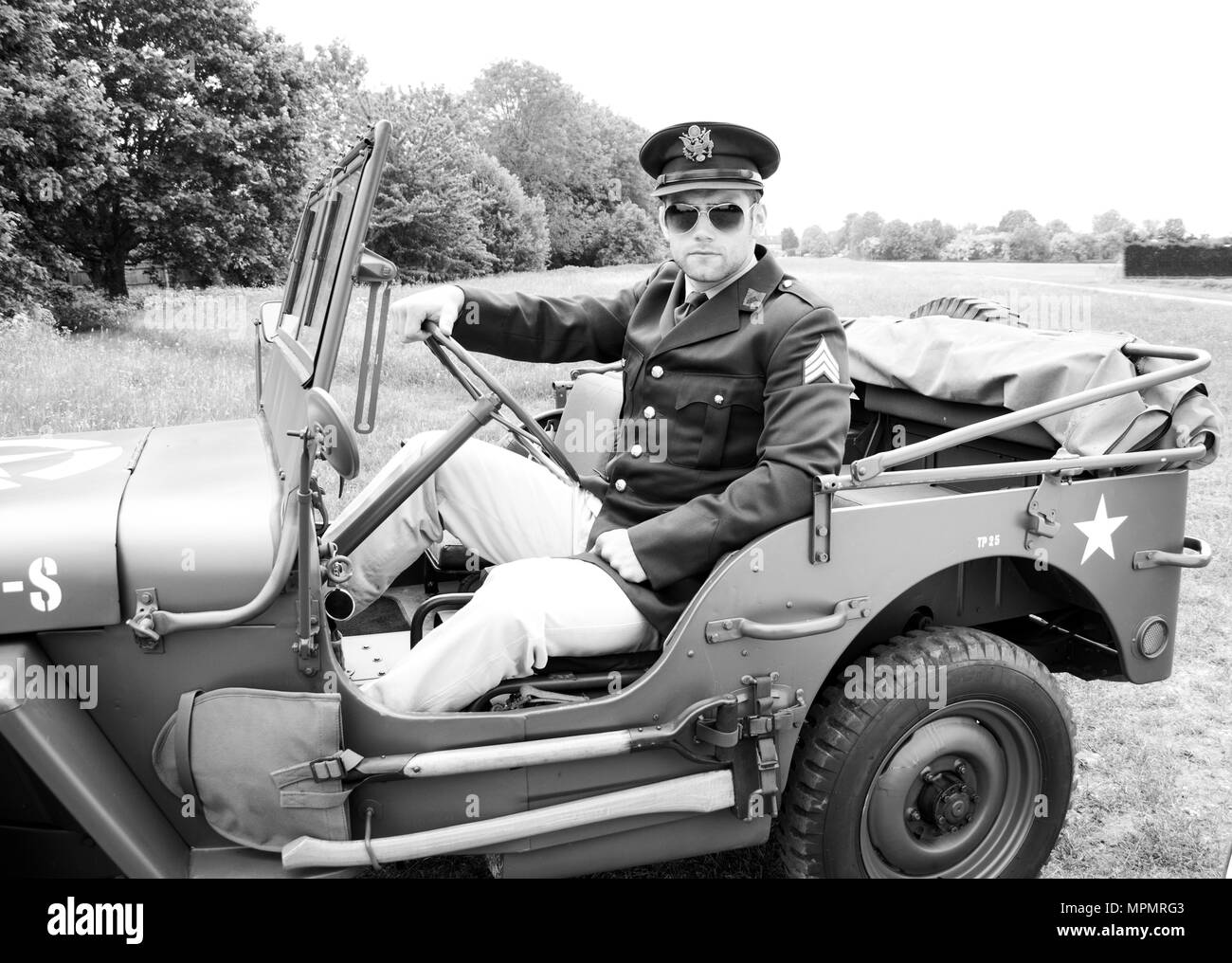 Handsome American WWII GI Army officer in uniform riding Willy Jeep - Stock Image