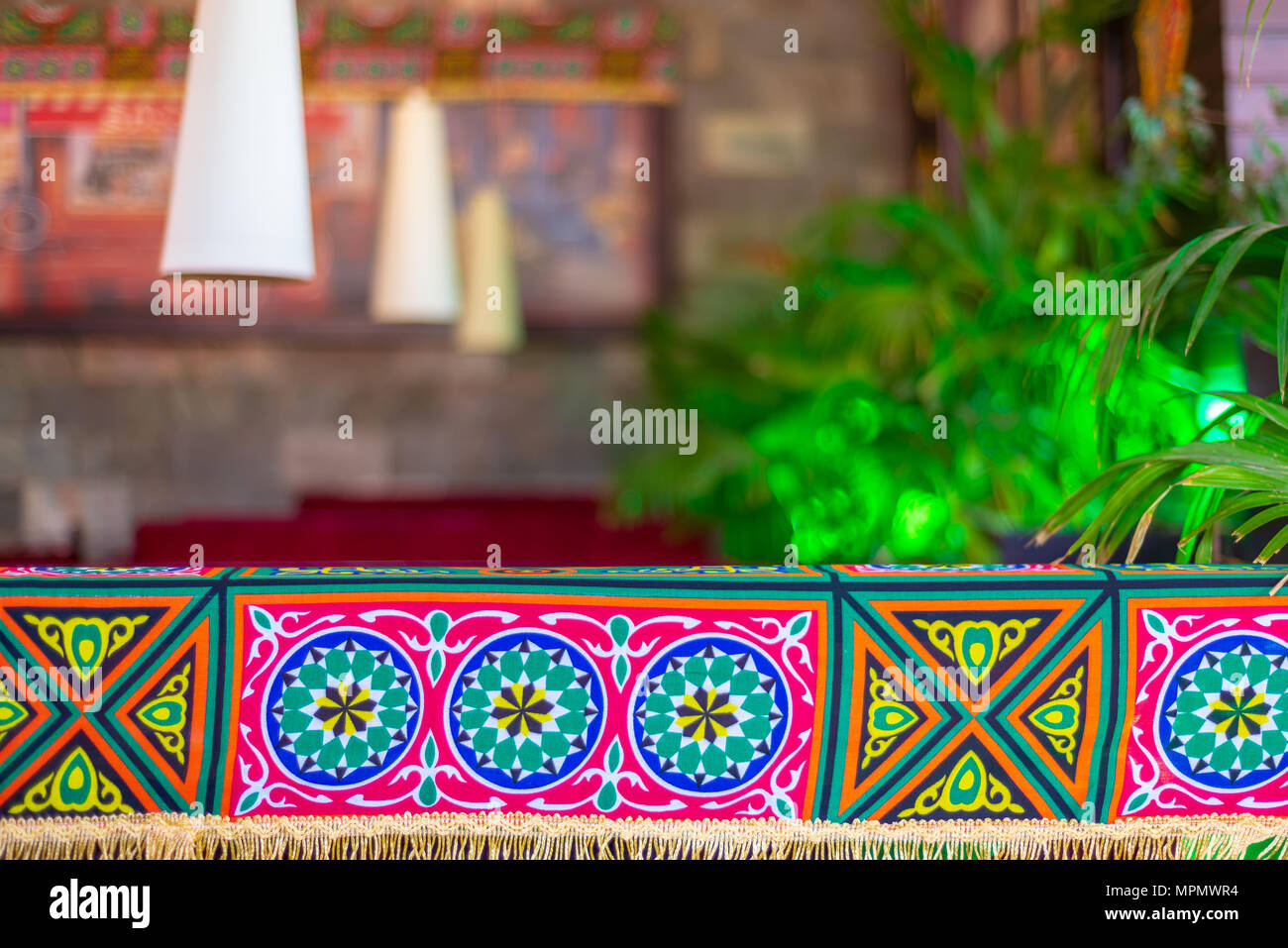 Traditional Ramadan decorations with blurry background of tables, lanterns, and green plants - Stock Image