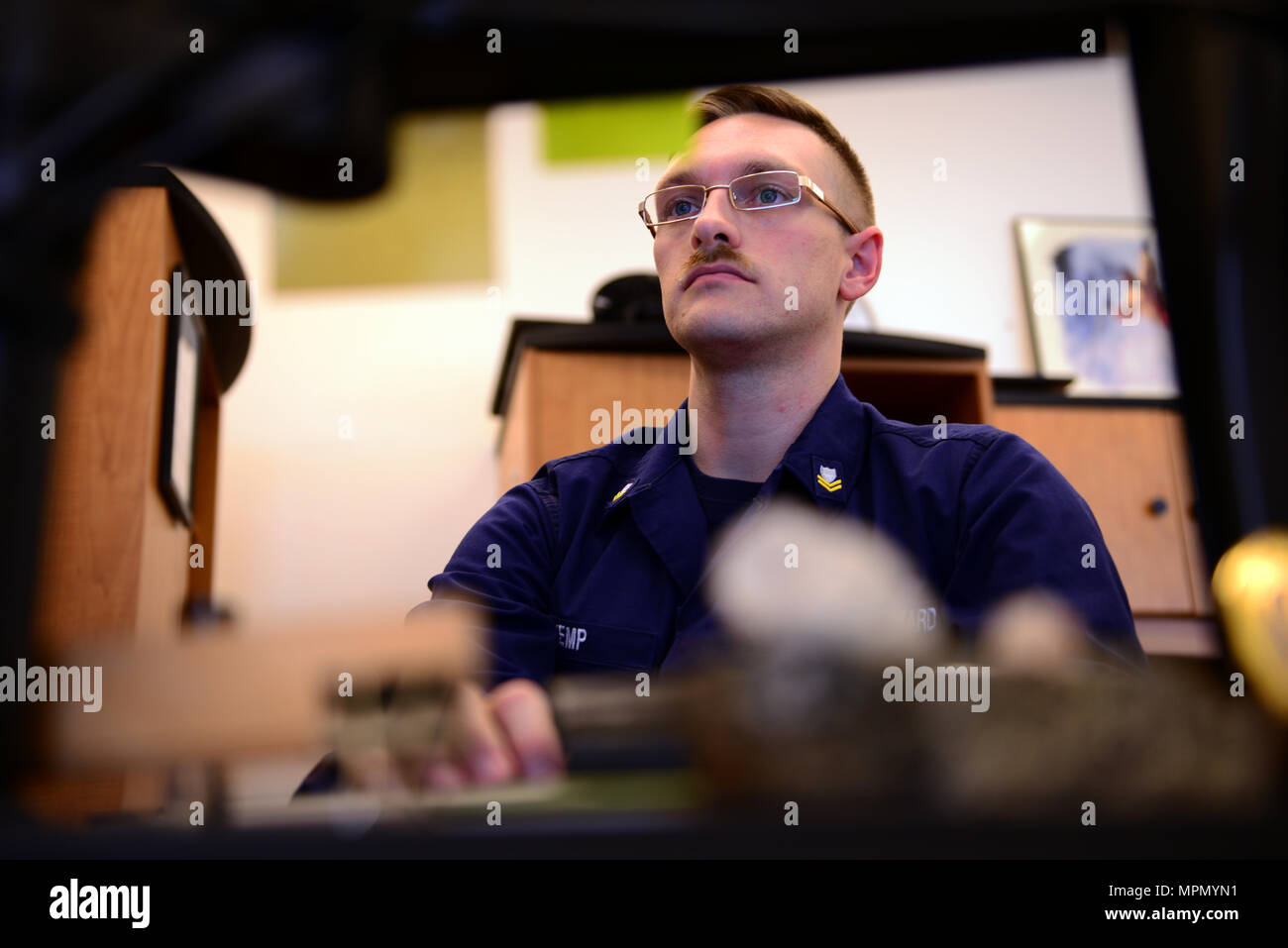Coast Guard Petty Officer 2nd Class Michael Cody Kemp, a storekeeper stationed with the 13th District, works at his computer, Feb. 16, 2017. At work, Kemp processes procurement requests, removes and records property, reconciles accounts and acts as a liaison with Coast Guard Base Seattle personnel for any of their financial needs. U.S. Coast Guard photo by Petty Officer 2nd Class Ali Flockerzi. - Stock Image