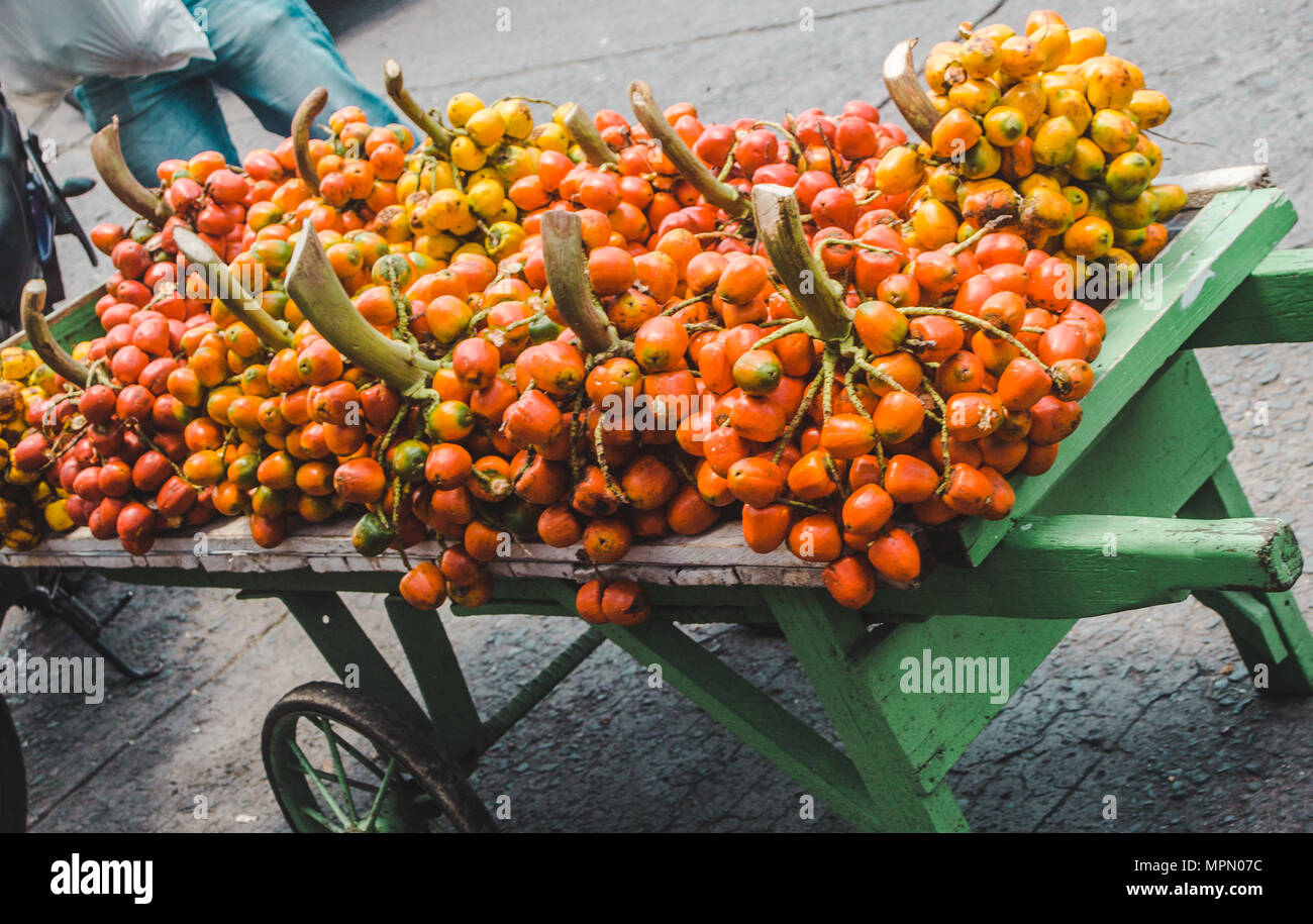 Orange Chunda Dura fruit piled on a green wooden market