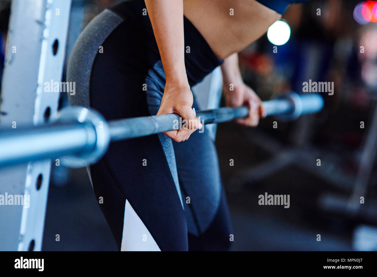 Woman lifting barbell in gym - Stock Image