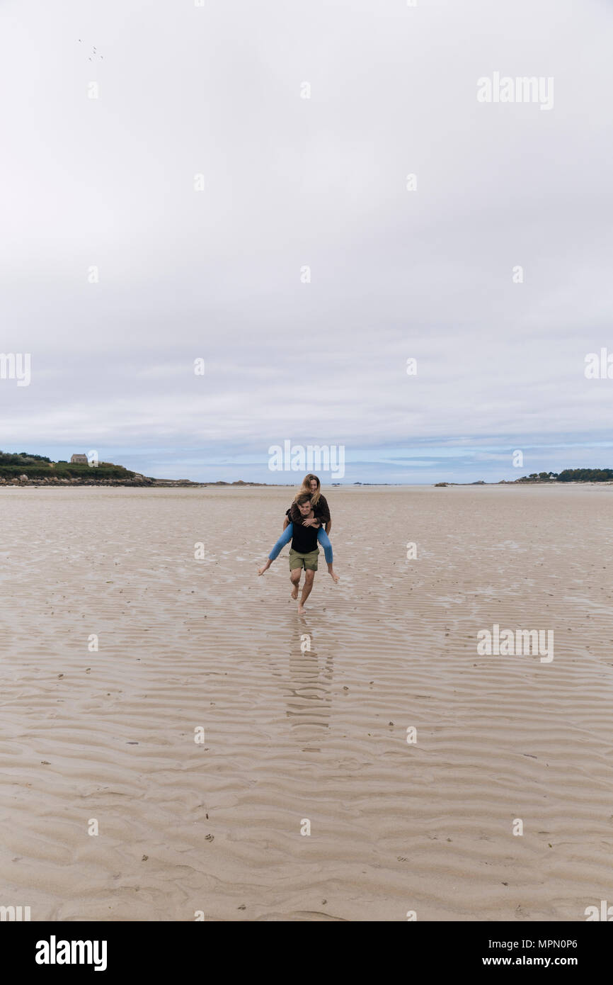 France, Brittany, Guisseny, young man running  carrying girlfriend piggyback on the beach Stock Photo