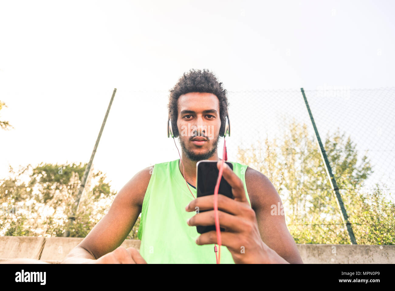 Basketball player listening music, smartphone and headphones - Stock Image