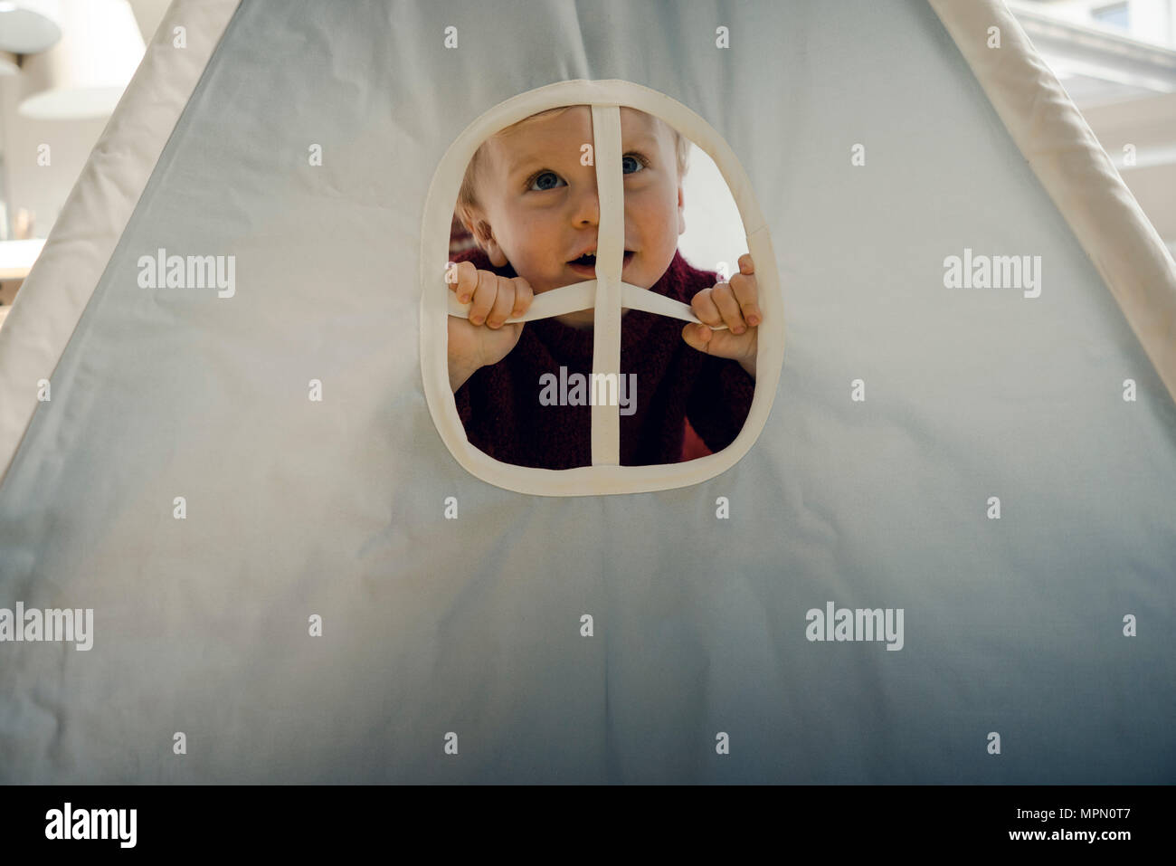 Little boy playing in tent, looking through window, laughing - Stock Image