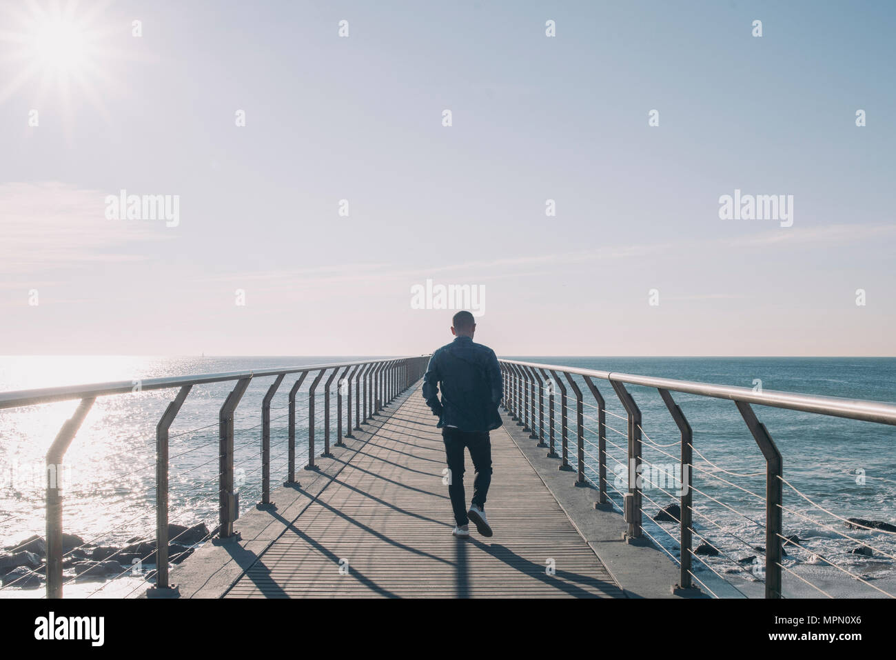 Back view of man walking on boardwalk at backlight - Stock Image