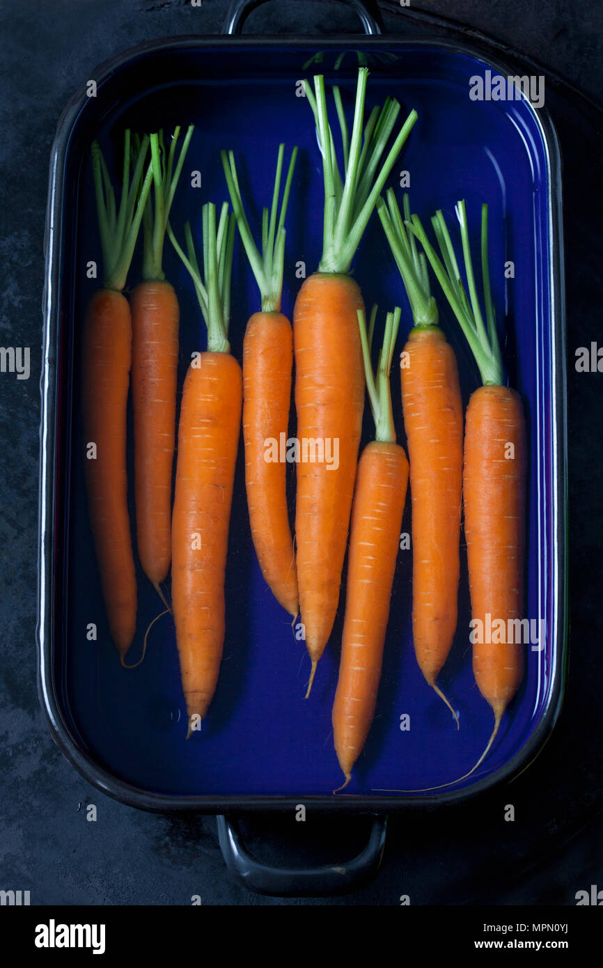Raw carrots in a roasting tray - Stock Image