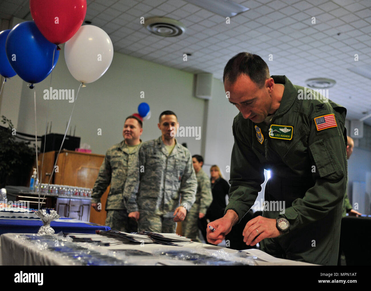 Col. Leonard Kosinski, 62nd Airlift Wing commander, fills out an Air Force Assistance Fund donation form at the AFAF kick-off event, April 6, 2017 at the McChord Field Chapel Support Center. Team McChord hopes to raise $51,576 in donations throughout the campaign, which lasts from April 10 through May 19. (U.S. Air Force photo/Staff Sgt. Whitney Amstutz) - Stock Image