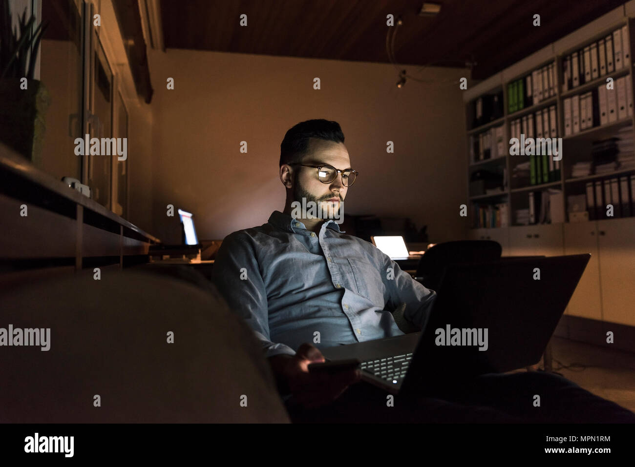 Businessman working on laptop in office at night - Stock Image
