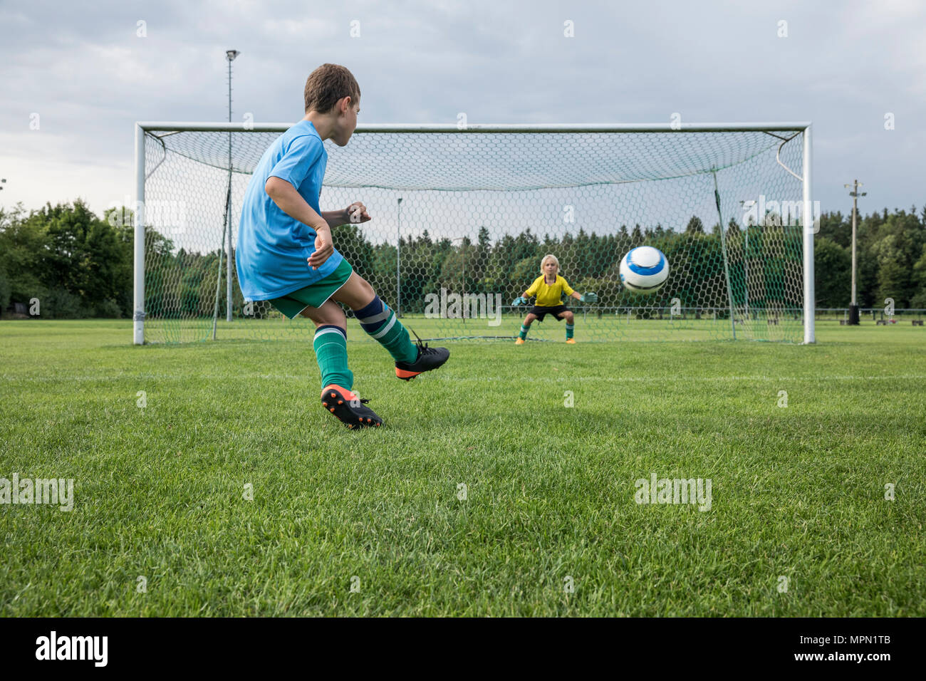 Young football player kicking ball in front of goal with goalkeeper - Stock Image