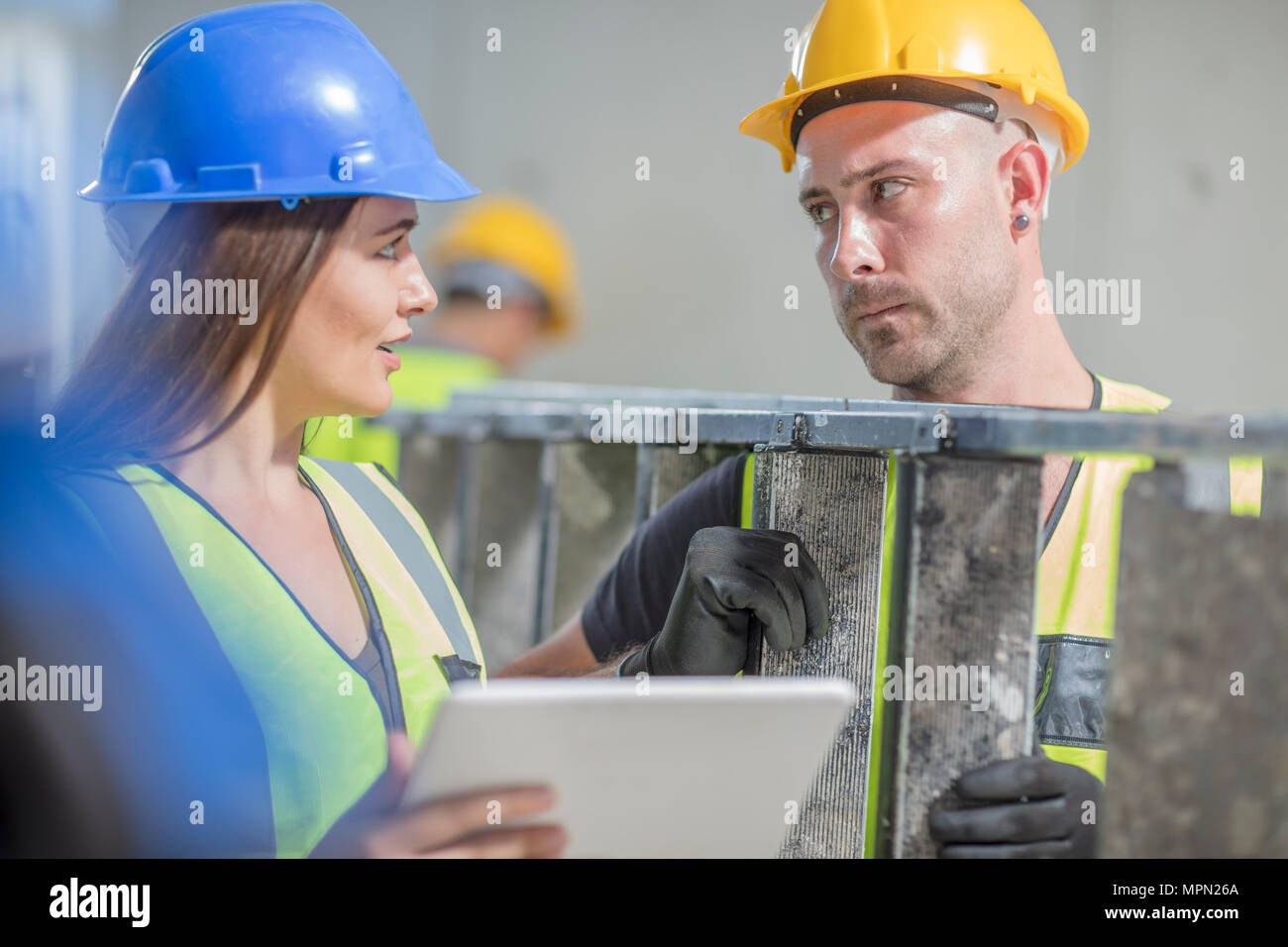Woman with tablet talking to man with ladder on construction site - Stock Image