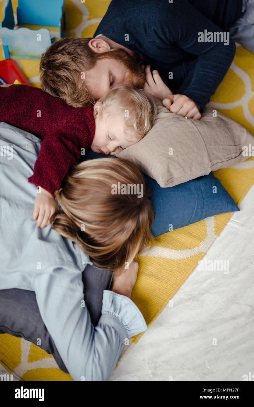 Tiered family resting together on the floor after playing Stock Photo