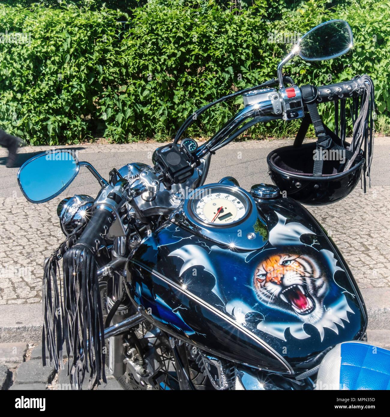 Berlin Mitte, Motor bike detail. Parked bike with tiger face, black helmet and leather tassles at  Bikers Demo. - Stock Image