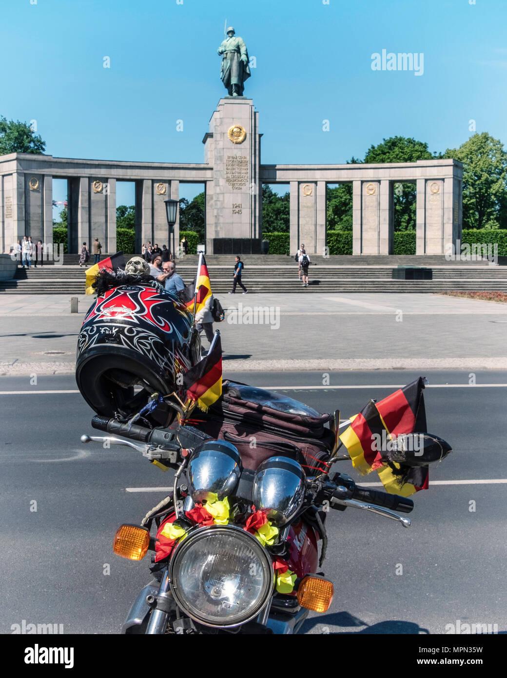 Berlin Mitte, Motor bike detail. Parked bike with German flags, helmet & skull in front of Soviet War Memorial  at Bikers Demo. - Stock Image