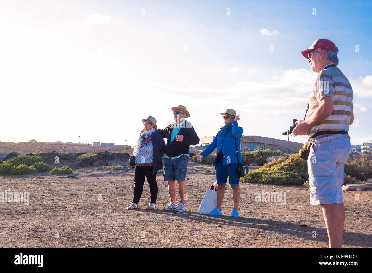 4 seniors spend free time on the beach watching and piloting the drone - Stock Image