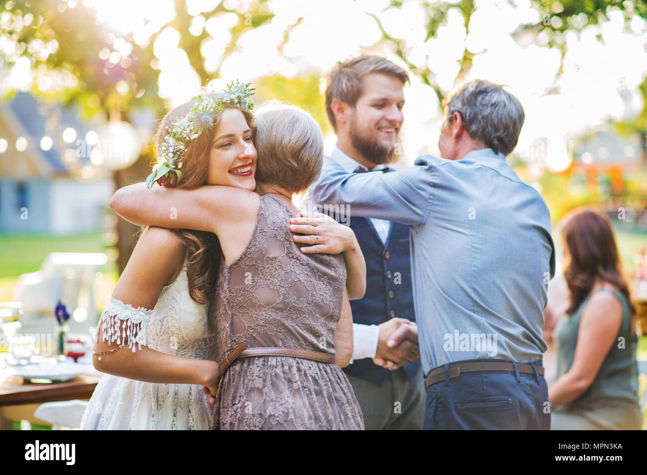 Guests congratulating bride and groom at wedding reception outside in the backyard. - Stock Image