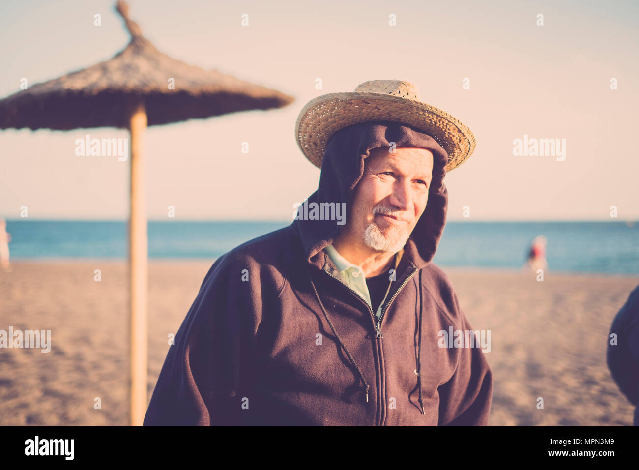 nice funny senior man with double hat at the beach in winter. vintge tones. smile and sunny light on his face - Stock Image