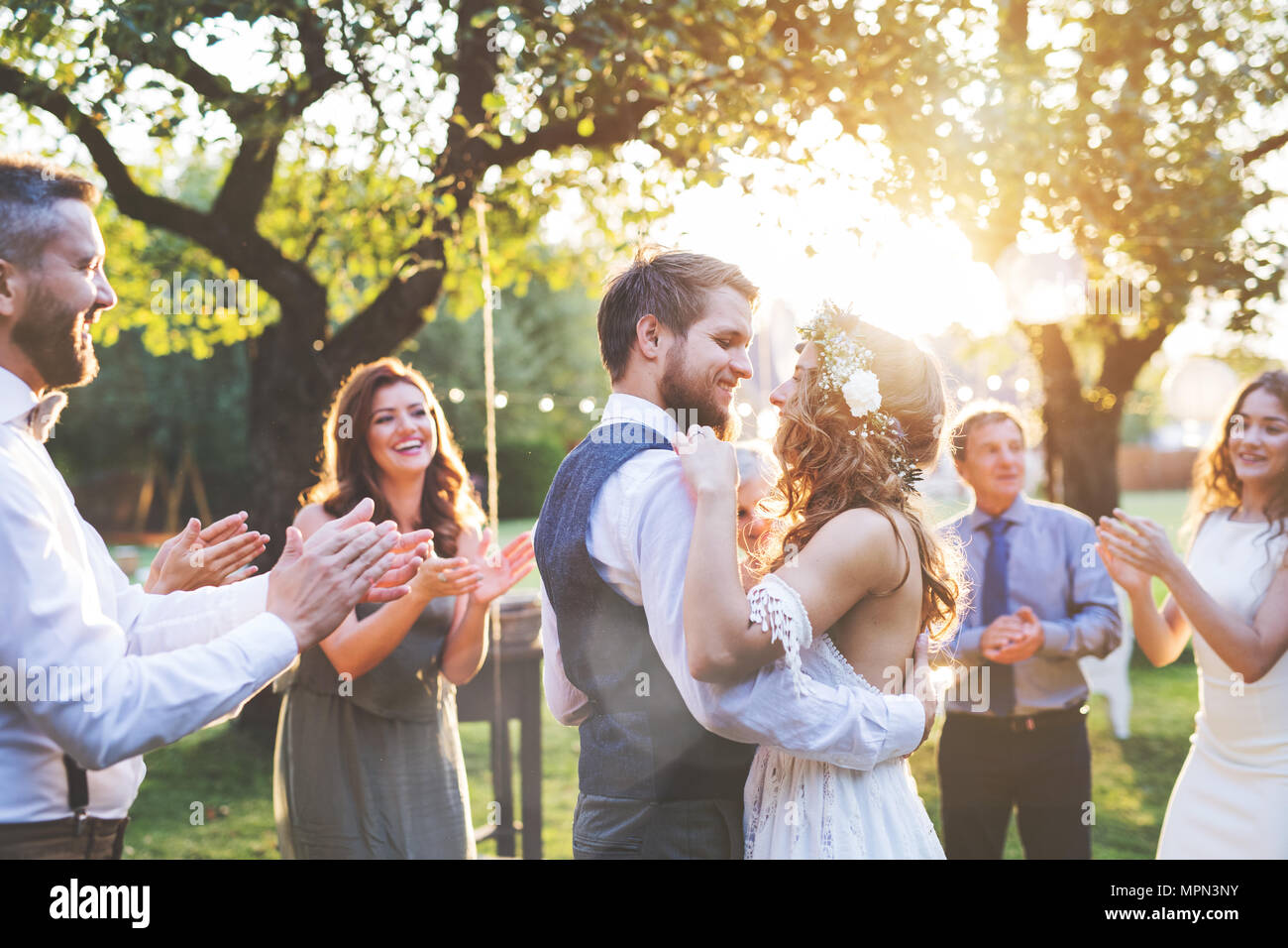 Bride and groom dancing at wedding reception outside in the backyard. - Stock Image