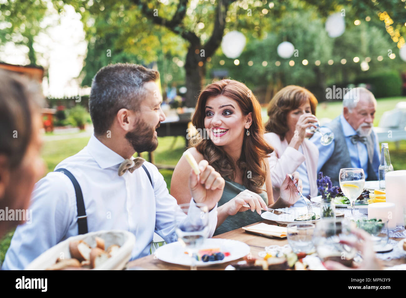 Guests eating at the wedding reception outside in the backyard. Stock Photo