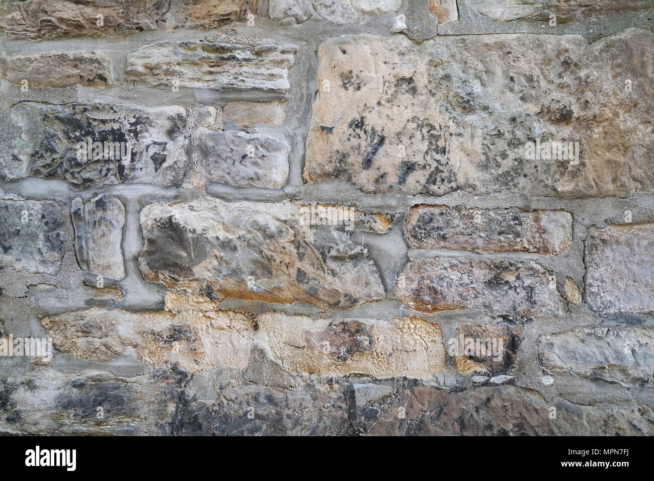 old weathered natural stone wall masonry background texture - Stock Image