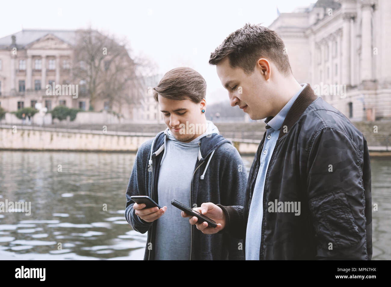 two antisocial mobile phone addicted male teenagers standing together using smartphone, technology concept, urban riverside location in Berlin Germany - Stock Image