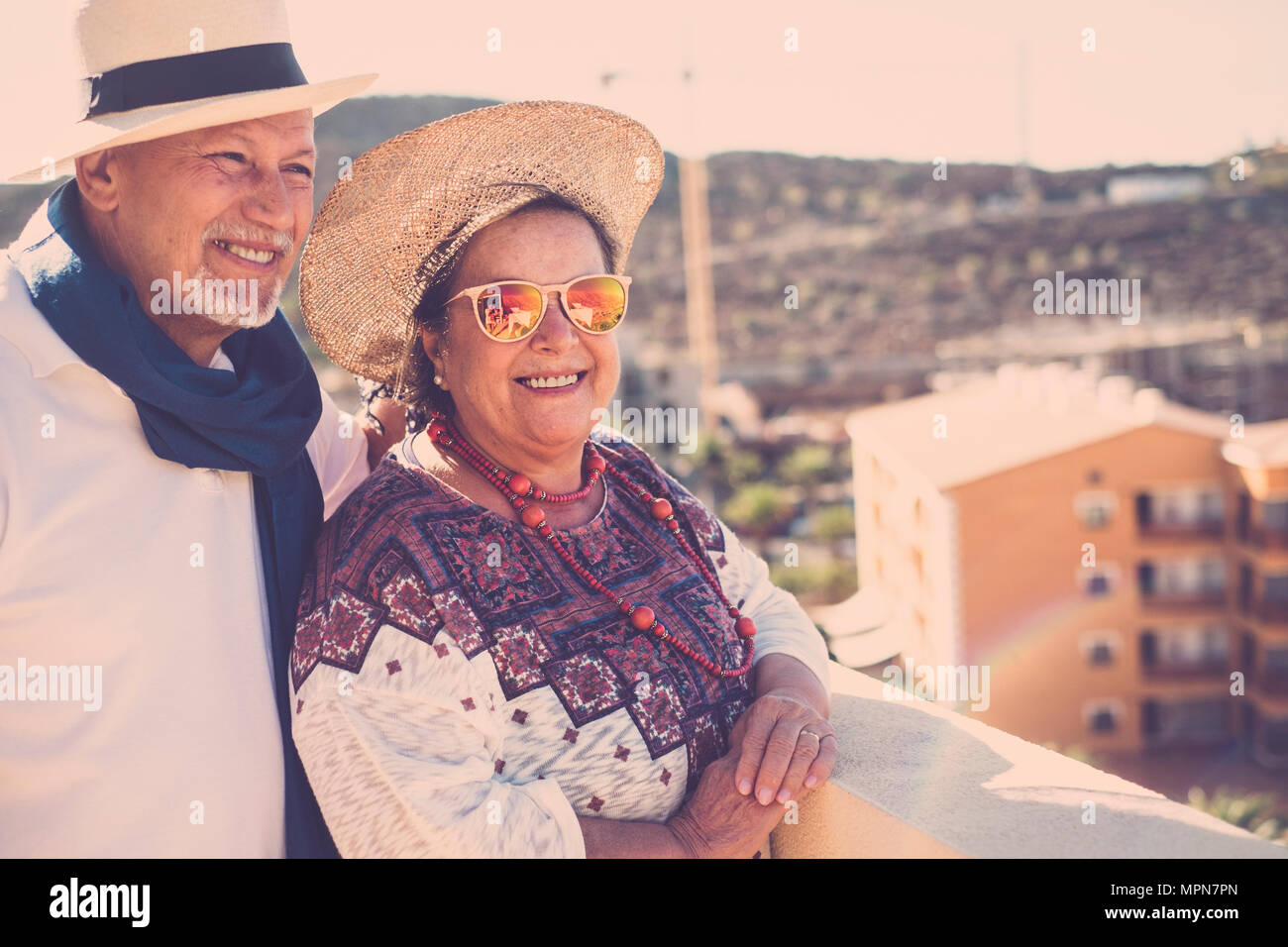 man and woman aged stay together with smiles and happiness on the terrace rooftop with nice view. sunlight and both with hats - Stock Image