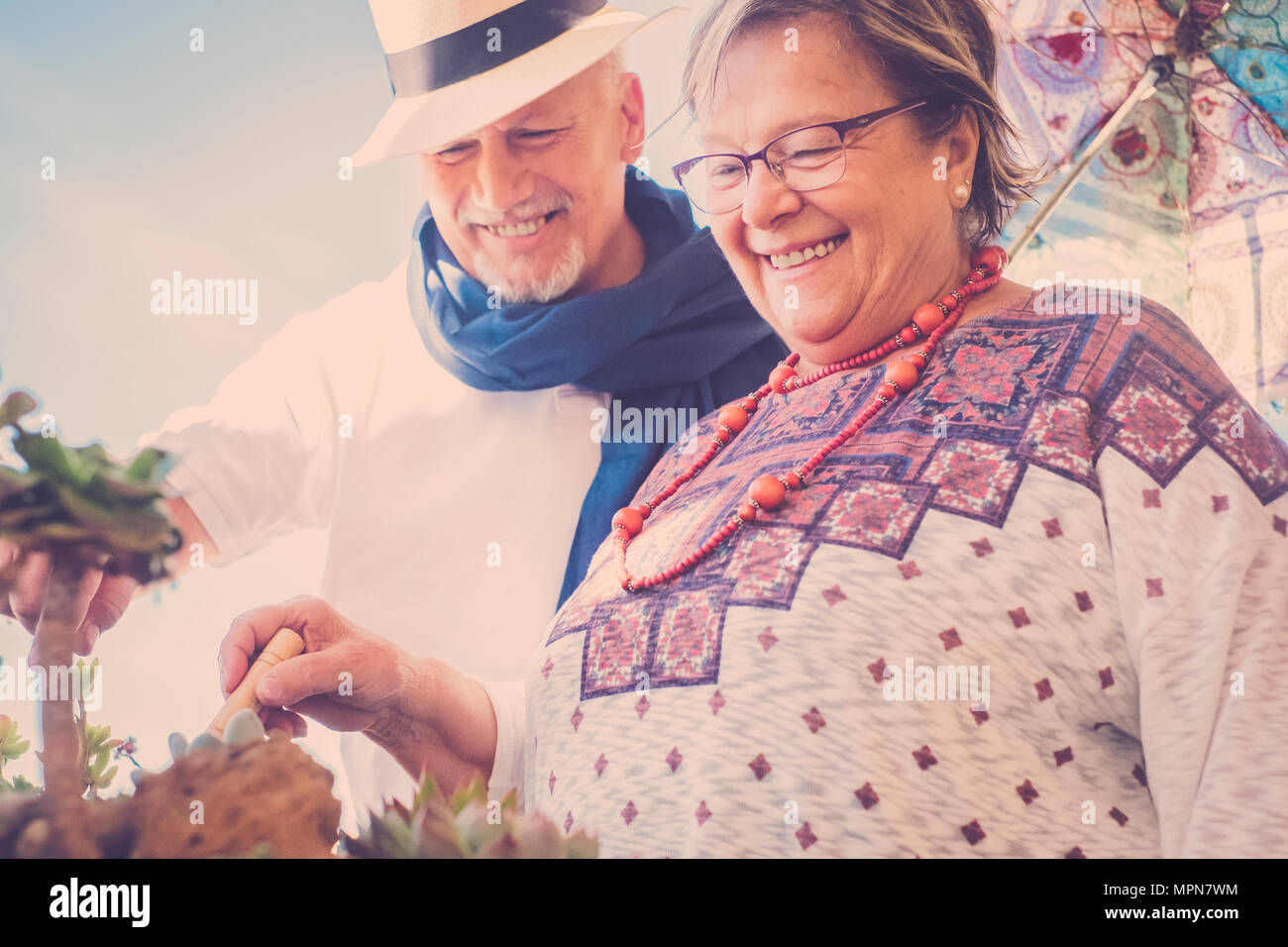 Senior man and woman elderly take care of the plants outdoor with ippy clothes and vintage filter for a retro look - Stock Image