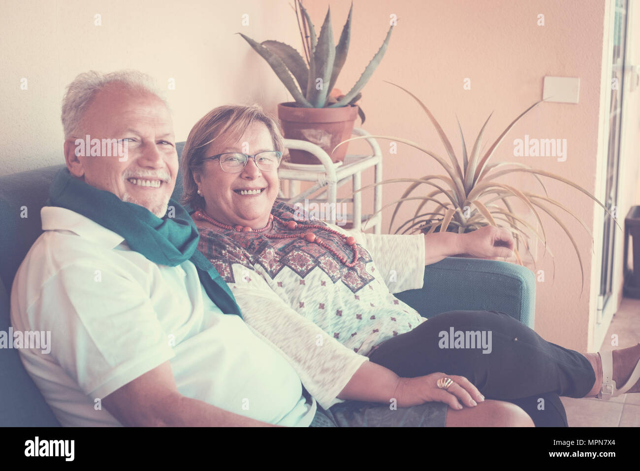 Elderly grandfather couple sitting on the sofa in the terrae. leisure nice time with fun and smiles. Vintage bright filter. - Stock Image