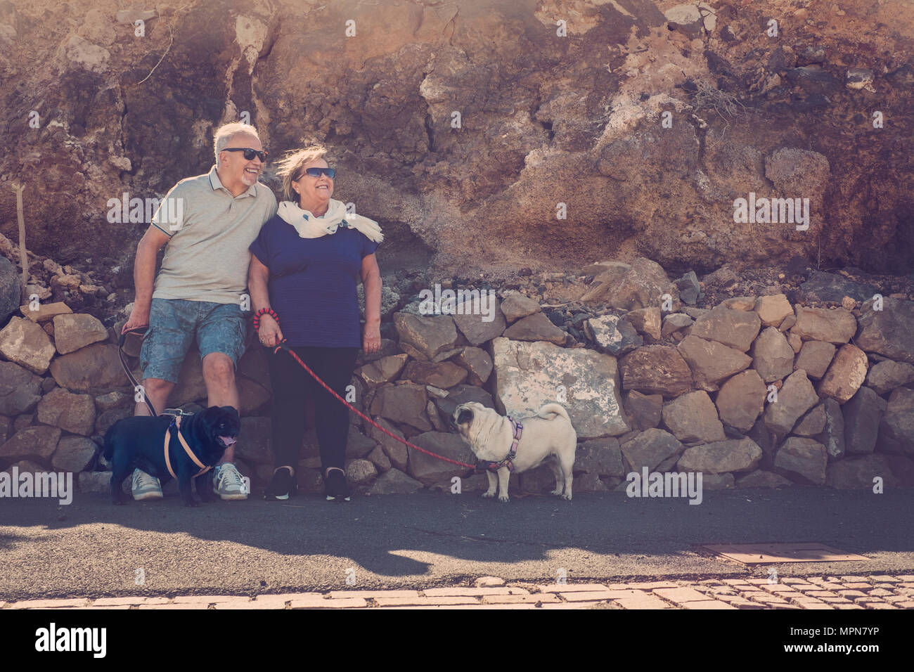 Elderly couple with two nice pugs cream and black ones. Sit down near a rocks mountain background. Looking at the sun in a beautiful day - Stock Image