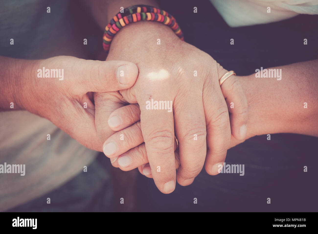 always tegether concept for a pair of elderly senior hands touching and staying together. Love moment for a life together Stock Photo