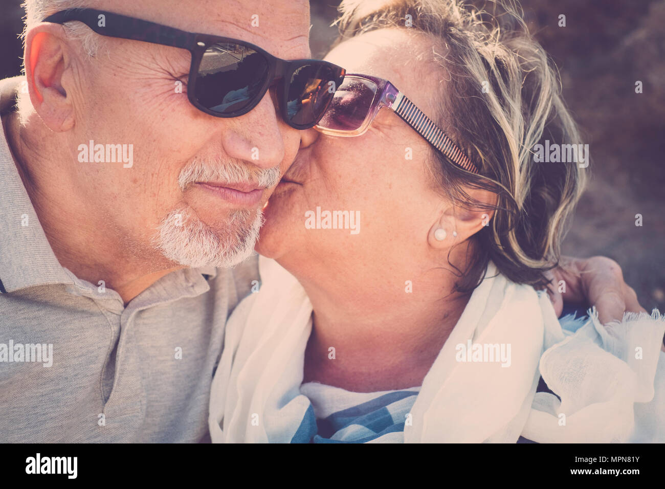 Nice love moments for two elderly woman and man kissing together with emotion. Close up scene of life to live forever. Smile and enjoy time. - Stock Image