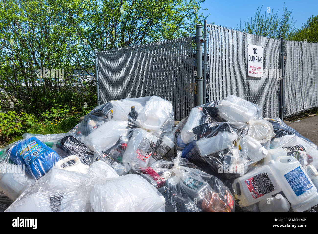 Rubbish dumped next to no dumping sign - Buckley Bay, British Columbia, Canada. - Stock Image
