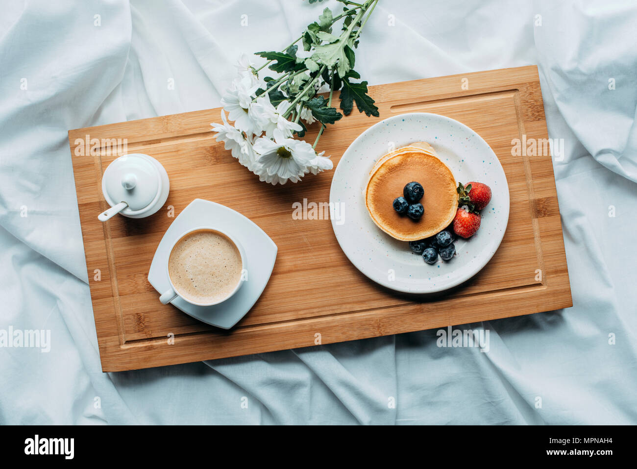 top view of breakfast in bed with delicious pancakes and coffee on wooden tray - Stock Image