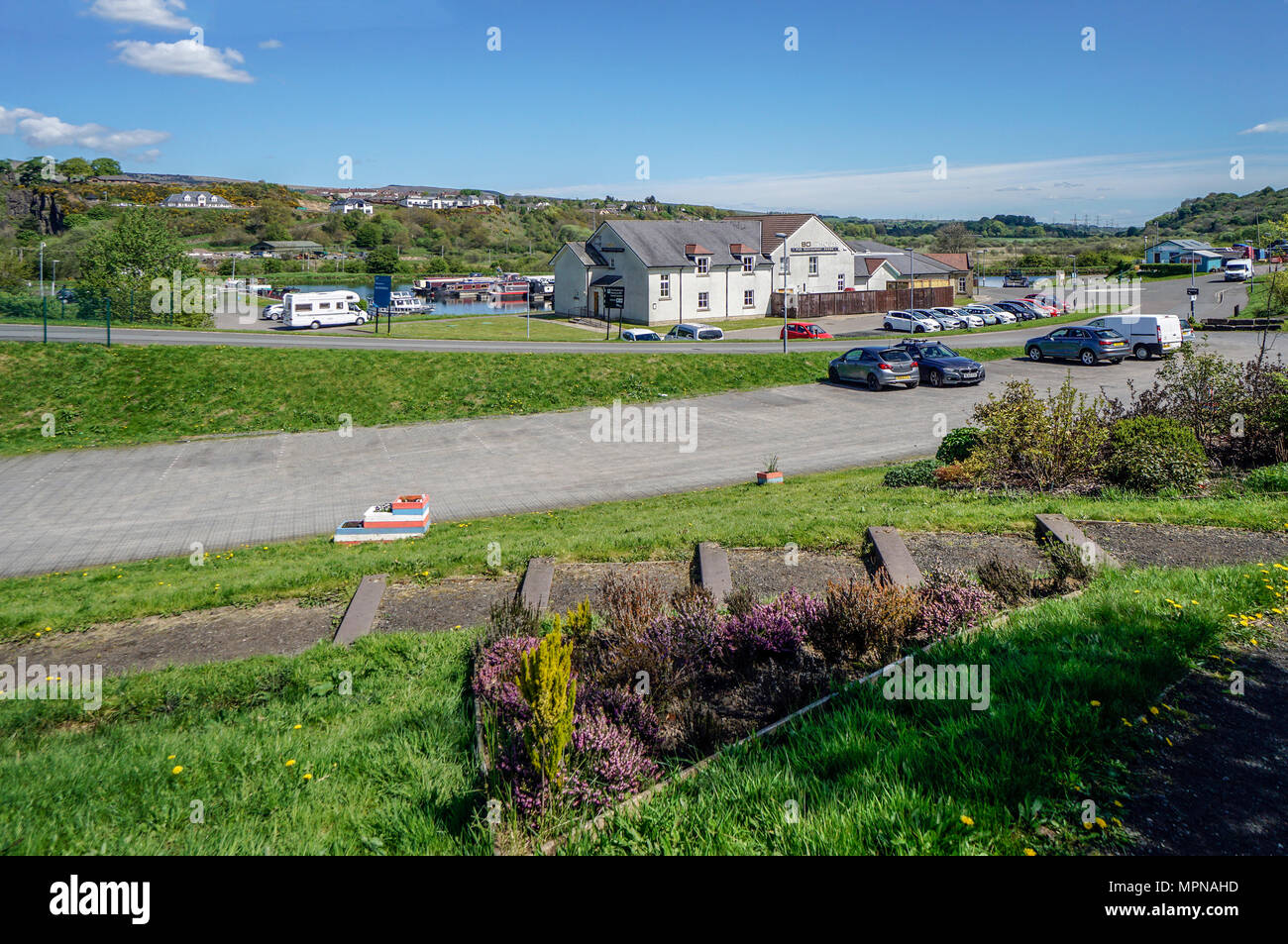 Boats moored in the basin on the Forth and Clyde Canal at village Auchinstarry near Kilsyth North Lanarkshire Scotland UK with The Boat House front. - Stock Image
