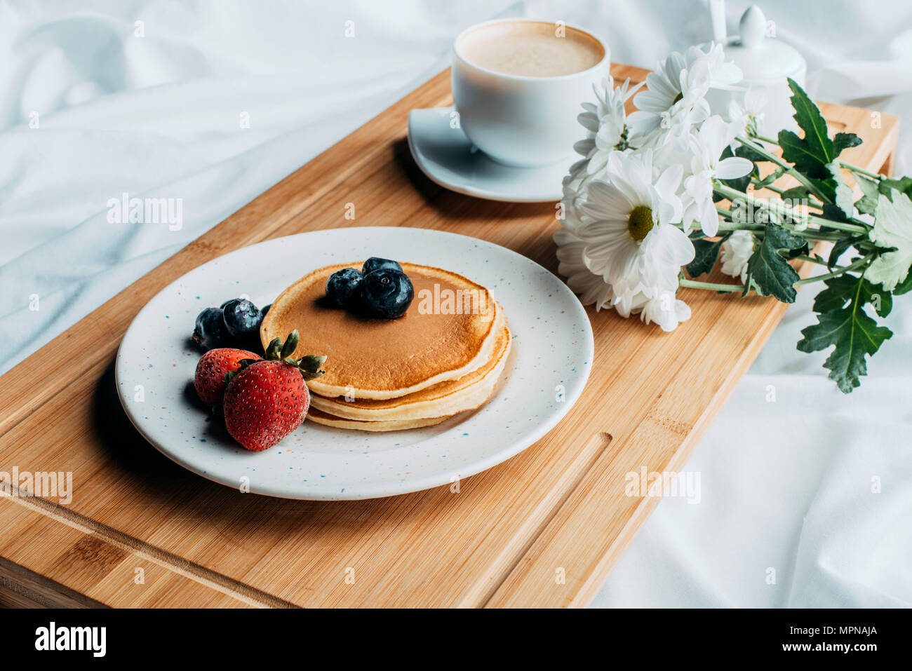breakfast in bed with pancakes and coffee on wooden tray - Stock Image