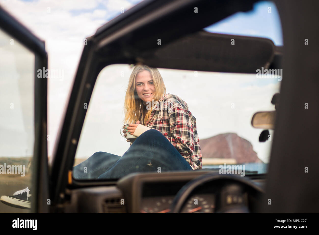 freedom and vacation concept for beautiful blonde caucasian young woman sitting down on the nose of a off road black car. Backlight and sunlight in wa - Stock Image