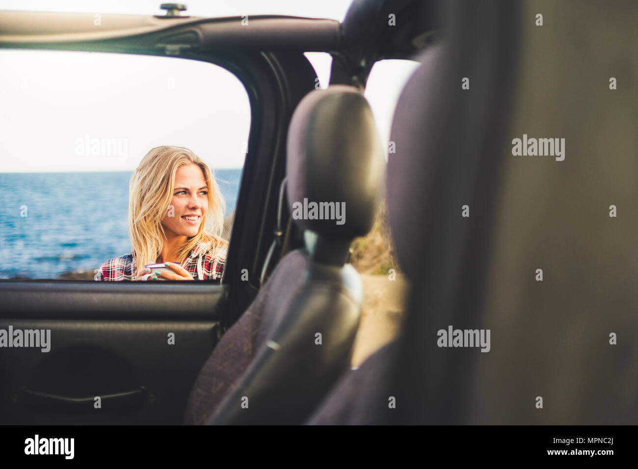 traveler blonde long hair girl take a mug with hot drink coffee or tea outside an open off road car. Ocean background and nice smile. Indipendent trav - Stock Image
