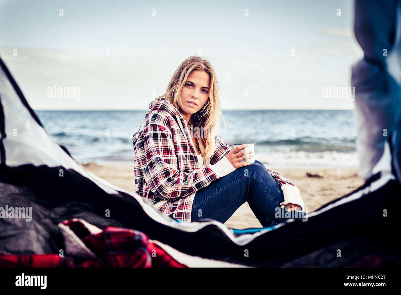 wild vacation alternative on the beach with a tent for a beautiful blonde female taking a mug with hot drink. Look at camera and rest. Alternative lif - Stock Image