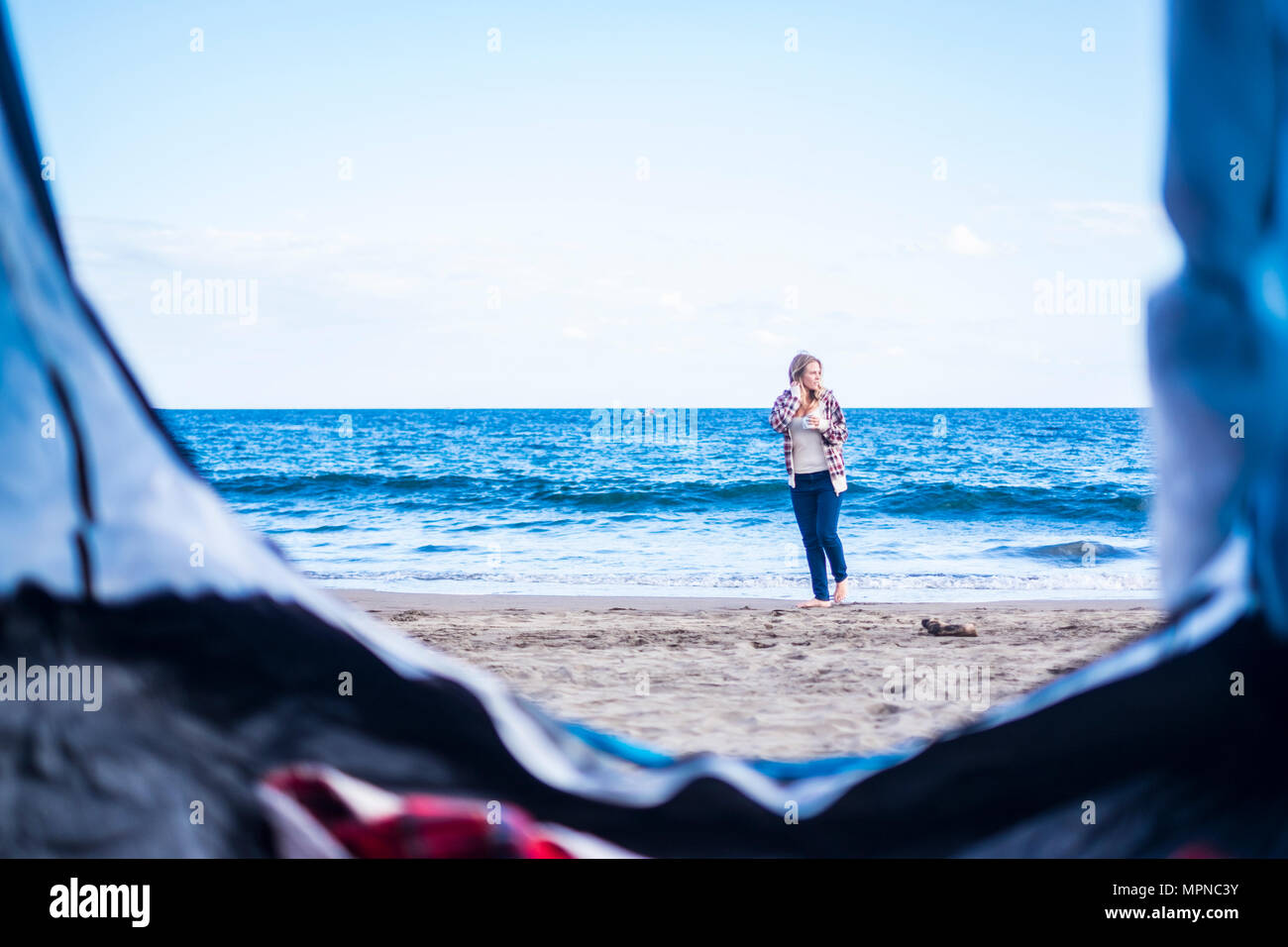 alternative life and vacation concept for blonde cute girl sit down looking at the ocean on the door of her tent. Tenerife locetion. - Stock Image