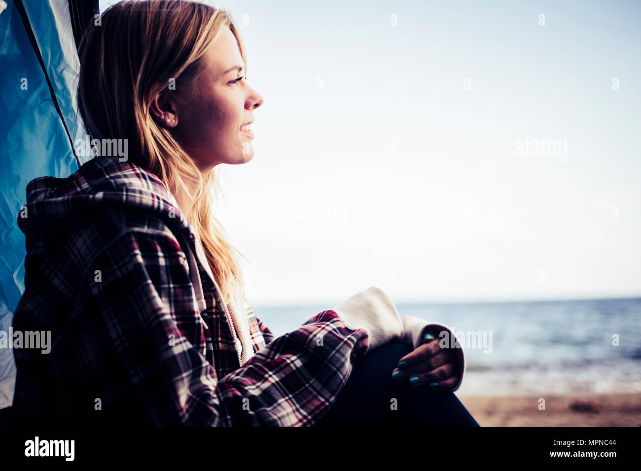 wanderlust for young beautiful blonde woman caucasian smiling at the ocean sit down of her tent placed on the beach. ocean and sea in the background - Stock Image
