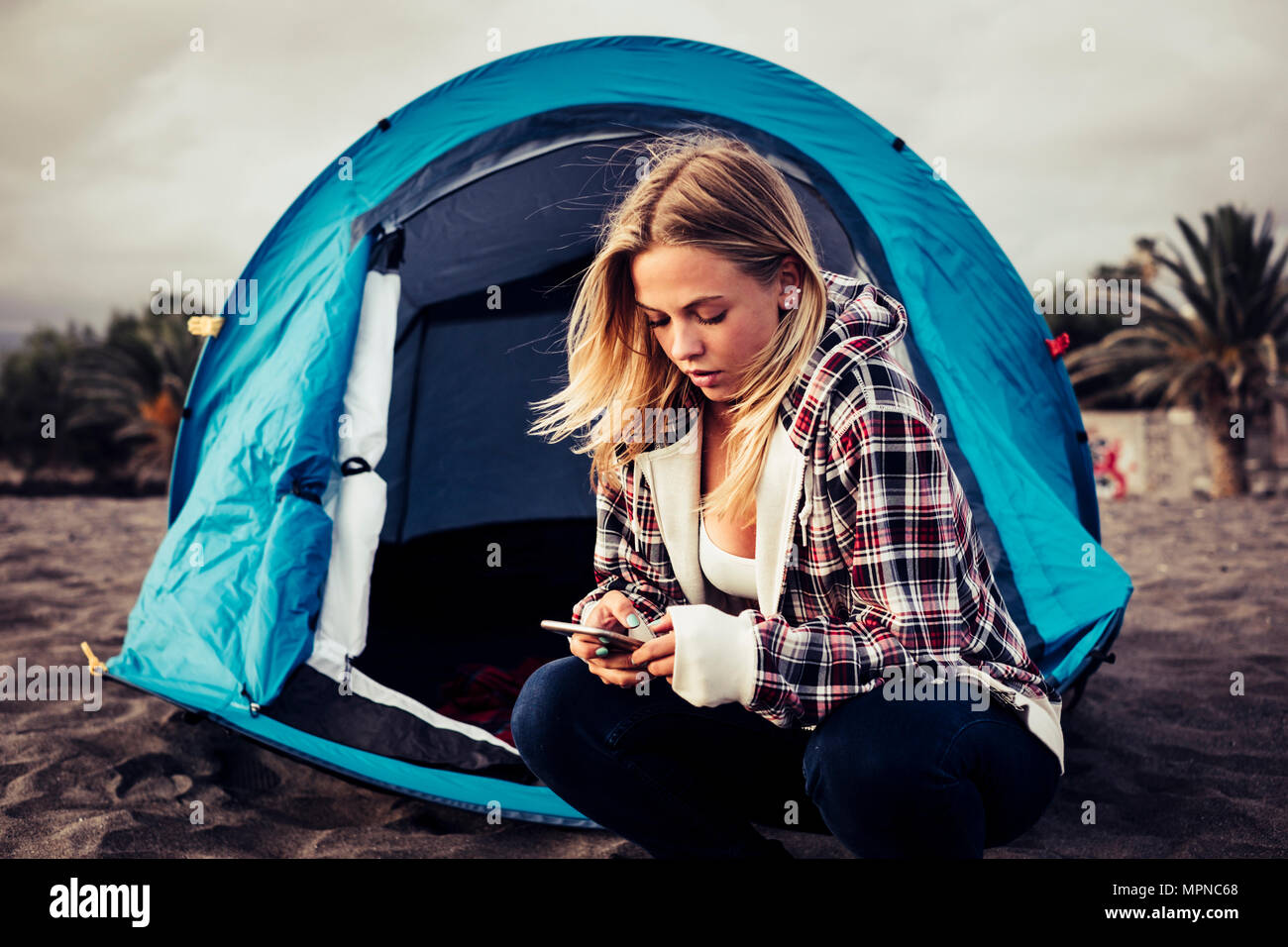 Always connected with technology blonde young woman stay ouside of her tent on the beach to enjoy freedom from work. - Stock Image