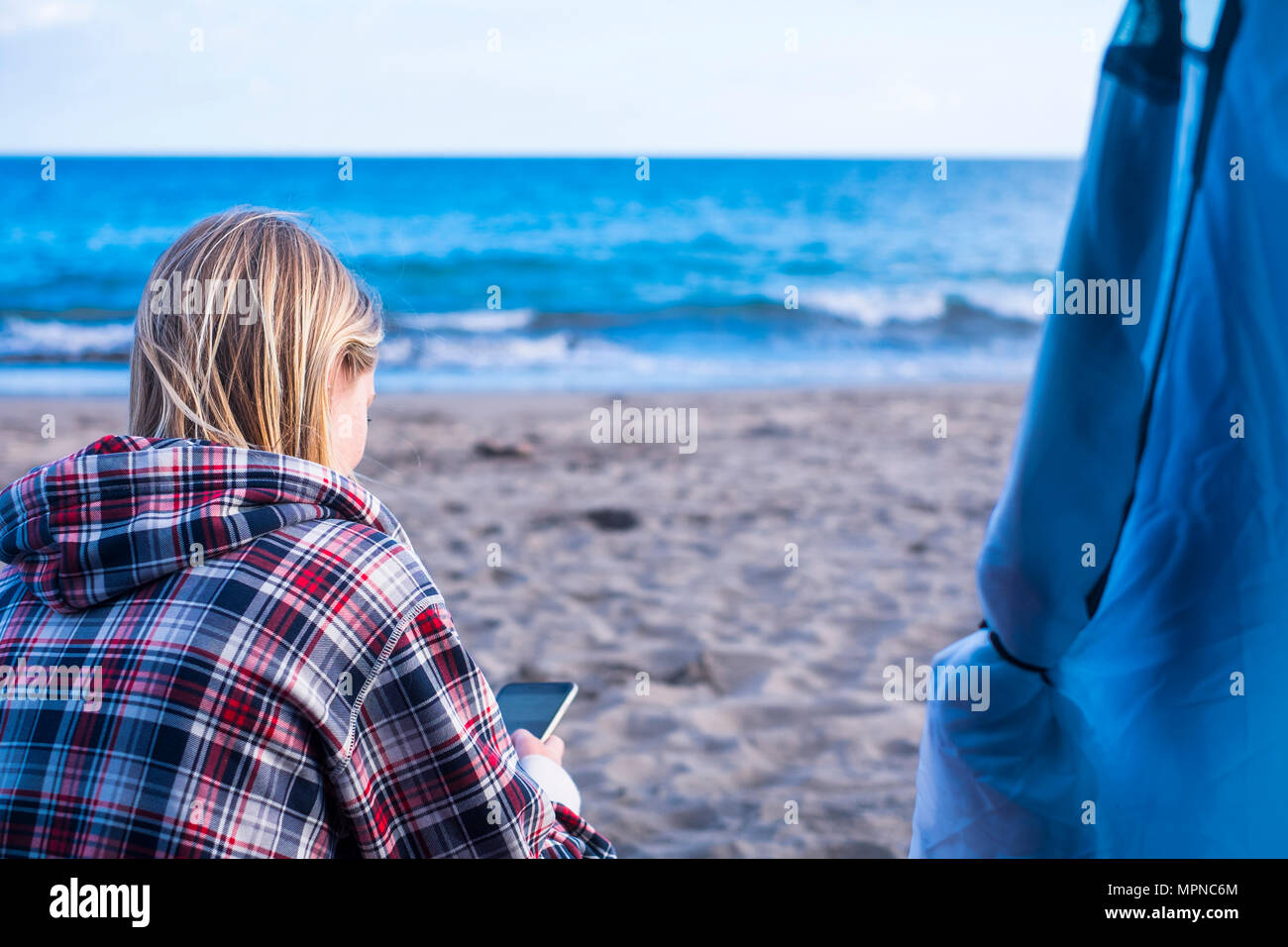 blonde beautiful woman sit down in spring on the beach out of the tent in free camping checking the phone for messages - Stock Image