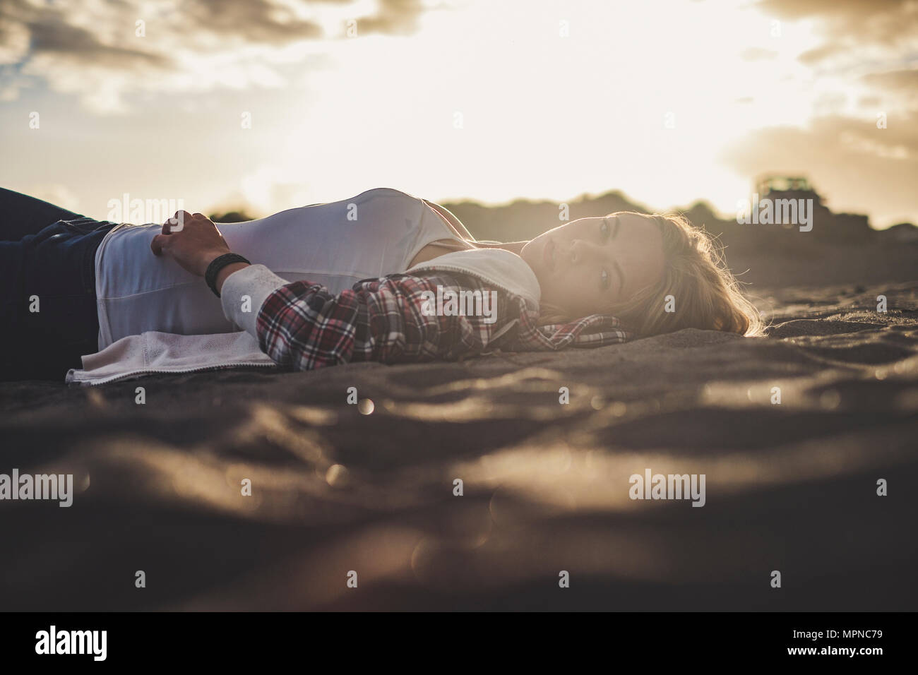 Beautiful sunset light for a cute blonde girl lay down rest on the beach in Tenerife. She look at you. Off road car parked on the background - Stock Image