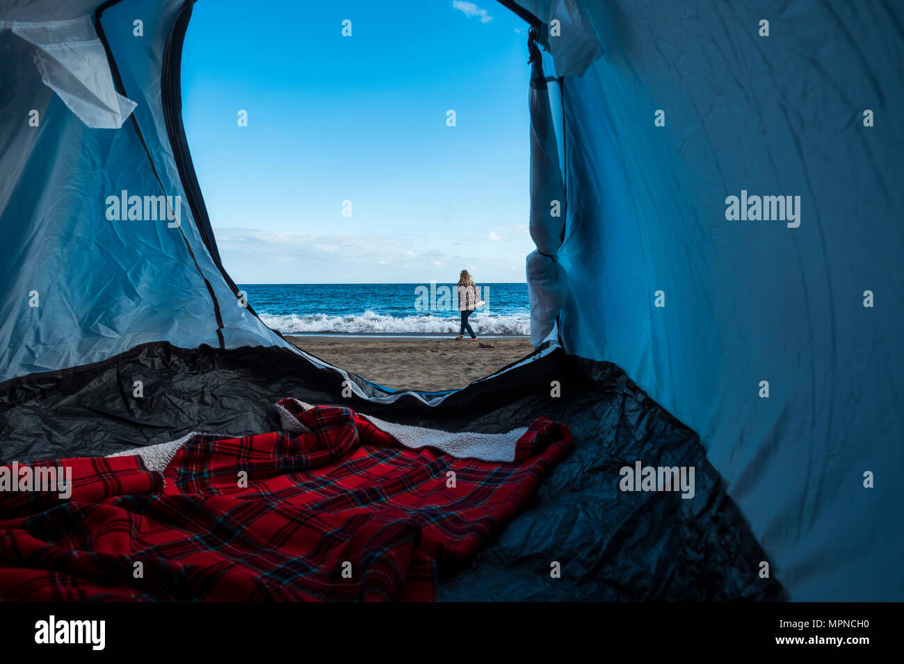 beautiful blonde woman sitting don outside the tent in free alternative vacation camping just on the beach close to the ocean. different lifestyle con Stock Photo