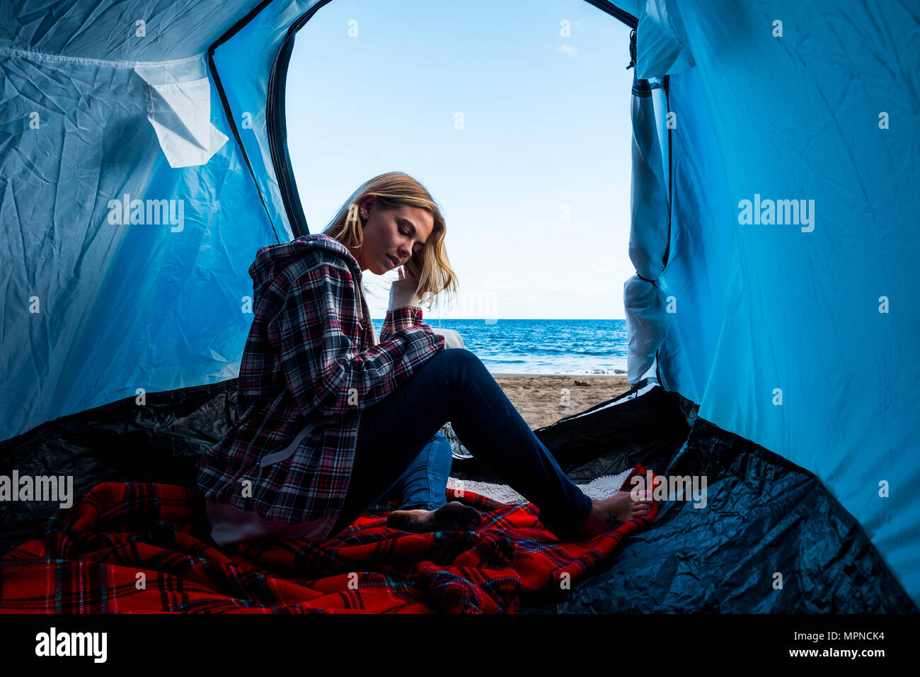 beautiful caucasian blonde young woman in a tent on the beach near the ocean live an alternative vacation lifestyle full of freedom and independence - Stock Image