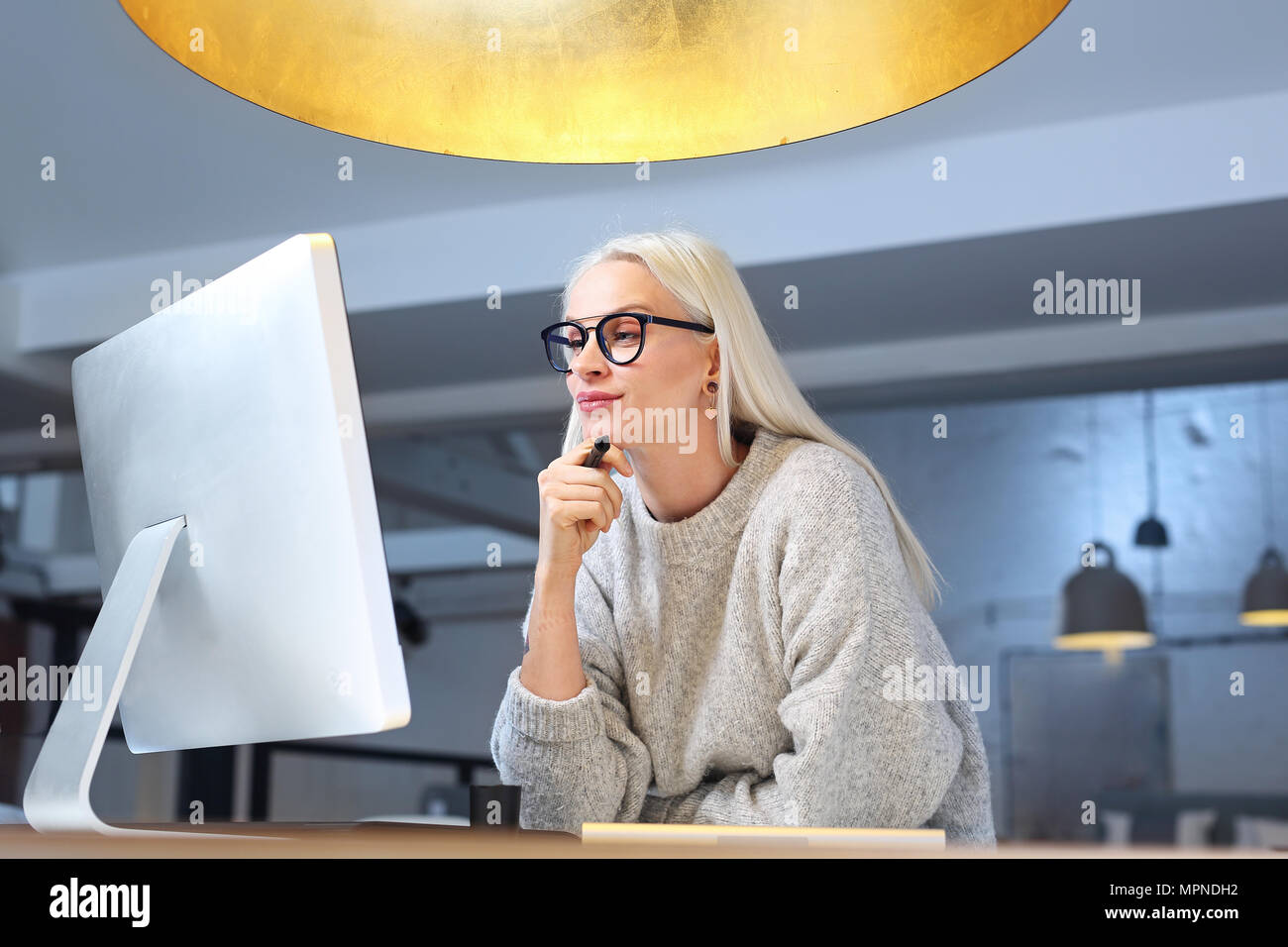 Work until late. The woman is working at the computer. - Stock Image