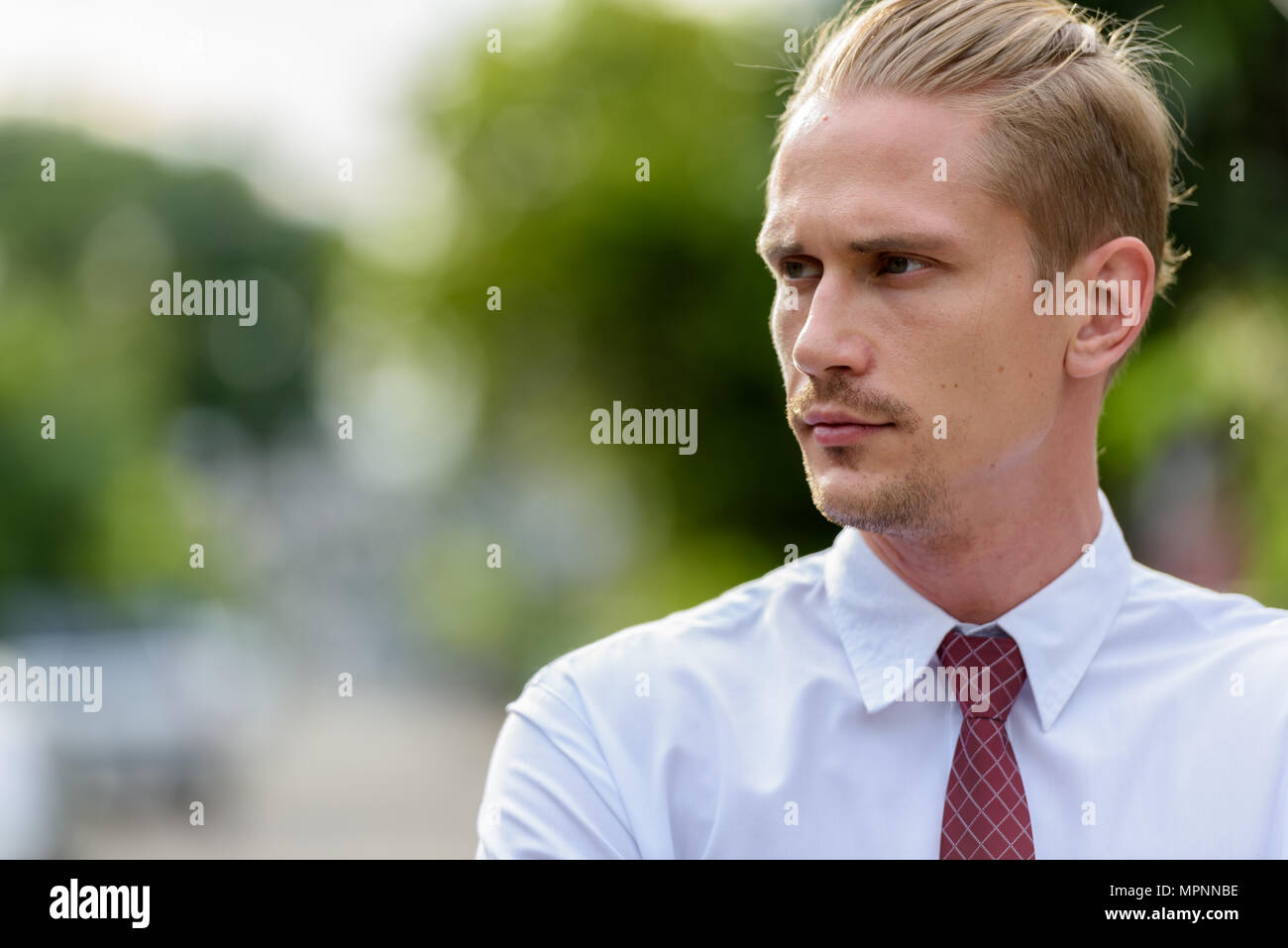 Close up of young handsome businessman thinking while looking at - Stock Image