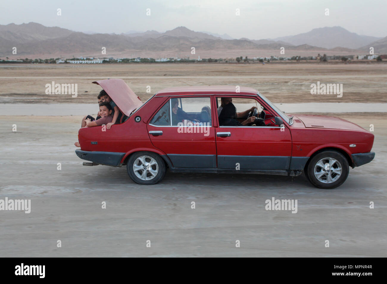 Local transport. A full car with children in the boot. Photographed in Dahab, Sinai, Egypt - Stock Image